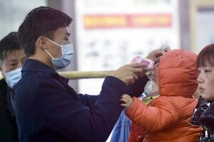 Pracovníci kontrolujú infračervenými teplomermi telesnú teplotu cestujúcim, ktorí prišli z čínskeho mesta Wu-chan do Chang-čou.