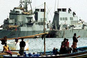 Na snímke z 28.októbra 2000 jemenskí rybári sa plavia na člne pri explóziou poškodenej americkej bojovej lodi USS Cole v jemenskom Adene.
