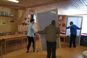 Deň pred voľbami. Spoločenskú miestnosť klienti Domoviny prestavujú na dočasnú volebnú miestnosť.