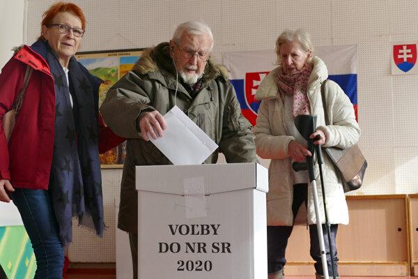 100-ročný vojnový veterán František Marek s dcérami počas vhadzovania obálky s hlasovacím lístkom do volebnej schránky.