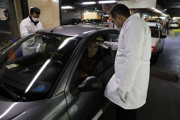 Iránski zdravotníci kontrolujú vodiča v teheráne.