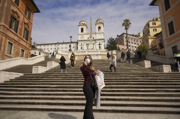 Žena s ochranným rúškom fotografuje pred Španielskymi schodmi v Ríme.
