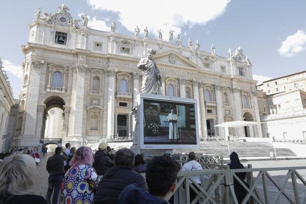 Veriaci sledujú pápeža Františka na celoplošnej obrazovke počas nedeľnej modlitby Anjel Pána na Námestí sv. Petra vo Vatikáne 8. marca 2020.