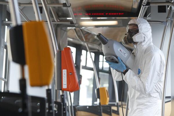 Pracovník v ochrannom obleku používa sprej obsahujúci nano polyméry na dezinfekciu električky v Prahe 12. marca 2020.