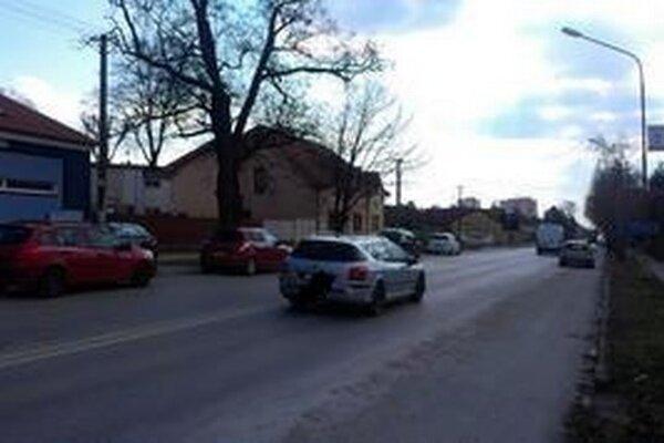 Po ľavej a pravej strany vozovky parkujú vozidlá.