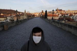 Mladý muž s ochranným rúškom na tvári kráča po Karlovom moste.