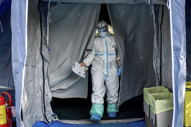 10. marec 2020: Zdravotník v ochrannom obleku vychádza z jedného stanov pred nemocnicou v talianskom meste Brescia.