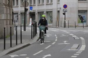 Žena s ochranným rúškom na tvári z dôvodu šíriaceho sa koronavírusu jazdí na bicykli v Paríži.