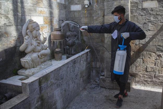 Kašmírsky dobrovoľník dezinfikuje priestor v hinduistickom chráme ako prevenciu pred šírením koronavírusu a ochorením COVID-19 v Šrínagare, indickej časti Kašmíru.
