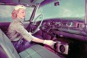 Dobová fotografia, na ktorej mladá slečna zapína klimatizáciu v osobnom automobile