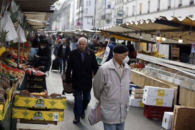 Muž s ochrannou maskou na tvári na trhu v Paríži.