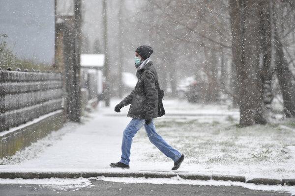 Muž s maskou, ktorú má na tvári na ochranu proti novému typu koronavírusu, kráča ulicou v maďarskom meste Debrecín 23. marca 2020.