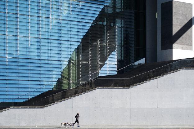 Osamelý muž behá s dvomi psami  pred budovou parlamentu vo vládnej štvrti v Berlíne.