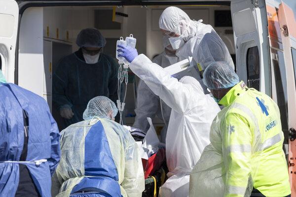 Pacient infikovaný koronavírusom COVID-19 je nakladaný do francúzskeho vojenského vrtuľníka.