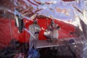 Dobrovoľníci z Červeného kríža triedia doma urobené ochranné rúška a distribuujú ich medzi ľudí v Prahe.