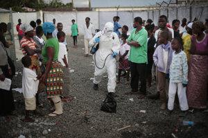 Zdravotník kropí dezinfekciou zem pri nohách ľudí, ktorých prepustili z kliniky pre liečbu eboly. (Monrovia, 30. september 2014)