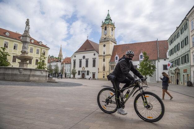 Cyklista s ochranným rúškom prechádza cez Hlavné námestie.