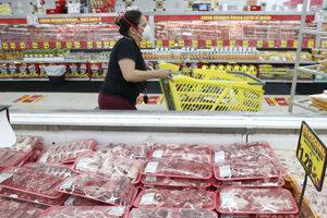 Zákazníčka s ochranným rúškom pozerá v časti mäsiarenskych produktov počas nakupovania v potravinách v Dallase.