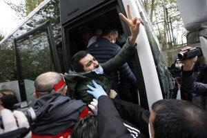 Demonštranta tlačia do policajného autobusu v Istanbule.