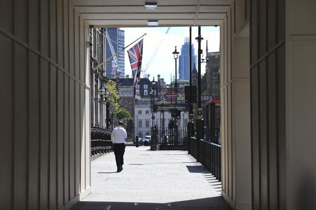 Muž kráča po prázdnej Parliament Street v Londýne.