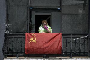 Podporovateľka komunistickej strany stojí na balkóne zdobenom bývalou sovietskou vlajkou počas karantény v ruskom Sevastopole.