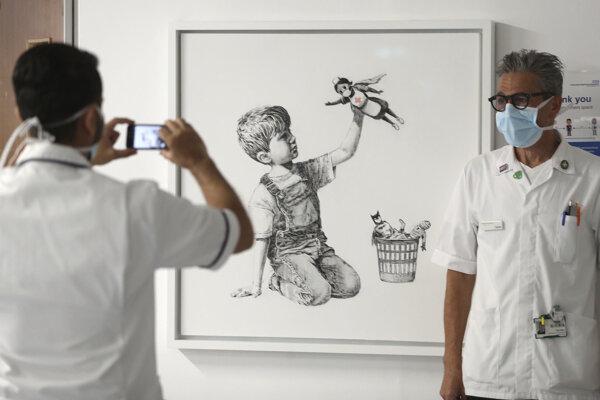 Zamestnanci sa fotia pred novým dielom známeho britského streetartového umelca Banksyho, ktorý si uctil v čase pandémie koronavírusu prostredníctvom svojej maľby  zdravotníckych pracovníkov v nemocnici v meste Southampton.