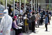 Ľudia s ochrannými rúškami na zabránenie šírenia nového koronavírusu čakajú na testovanie v testovacom centre na ochorenie COVID-19 spôsobeného koronavírusom v Itchewone.
