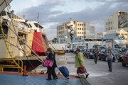 Cestujúci s rúškami nastupujú do trajektu v prístave Piraeus neďaleko Atén.