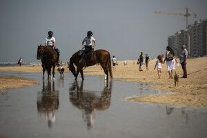 Policajti na koňoch upozorňujú ľudí, aby si nesadali na pláži počas hliadkovania pri pobreží Severného mora v rámci uvoľnenia opatrení prijatých na zabránenie šírenia nového koronavírusu v meste Oostende na severe Belgicka.