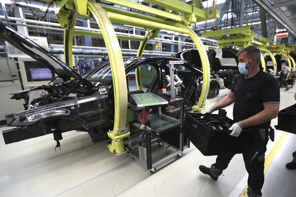 Zamestnanec s ochranným rúškom počas výroby automobilov Mercedes-Benz triedy S v závode v nemeckom meste Sindelfingen vo štvrtok 30. apríla 2020. Vlastníkom luxusnej značky automobilov Mercedes-Benz je nemecká automobilka Daimler.
