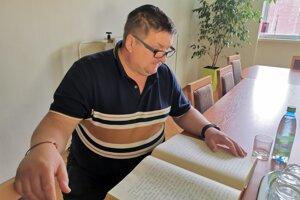 Starosta Kolačkova číta z kroniky, kde sú zaznamenané udalosti spred 10 rokov.