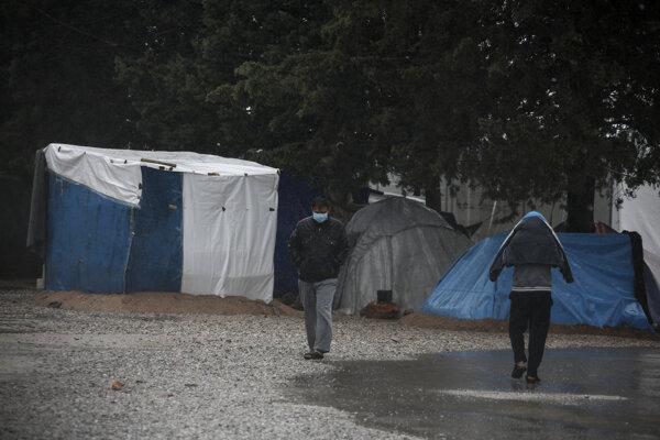 Migranti kráčajú v utečeneckom tábore v gréckej obci Malakasa.
