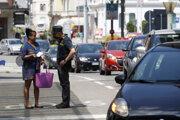 Žena hovorí s príslušníkom pohraničnej stráže na taliansko-švajčiarskej hranici.