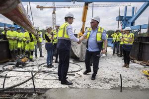 Minister dopravy Andrej Doležal a vpravo bývalý šéf rezortu dopravy Árpád Érsek po symbolickej úprave betónu na definitívnom spojení pravej a ľavej časti Dunajského súmostia.