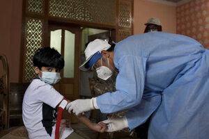Pracovník Svetovej zdravotníckej organizácie vyšetruje chlapca v Pakistane.