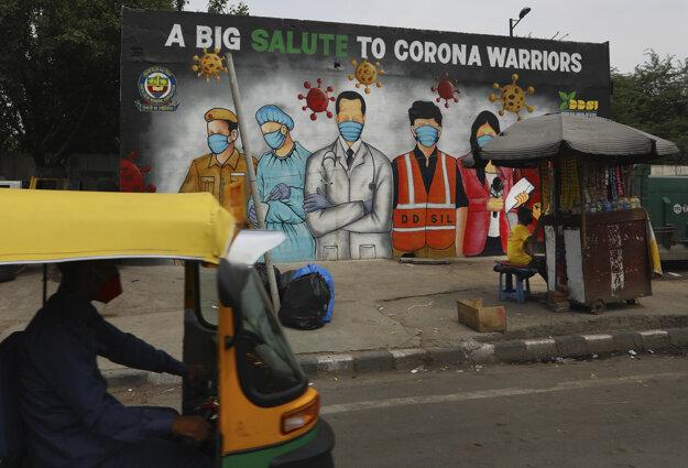 Auto-rikša v hlavnom meste Indie Naí Dillí prechádza popred graffiti maľbu, ktorá ďakuje ľuďom, ktorí bojujú proti koronavírusu SARS-CoV-2 v prvej línii.