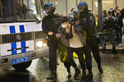 Ruská polícia zadržiava jedného z protestujúcich.