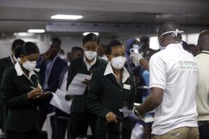 Nigérijský úradník používa teplomer aby preveril členov etiópskej leteckej posádky na prítomnosť vírusu COVID-19 po prílete na medzinárodné letisko Muhammeda Murtalu v Lagose.