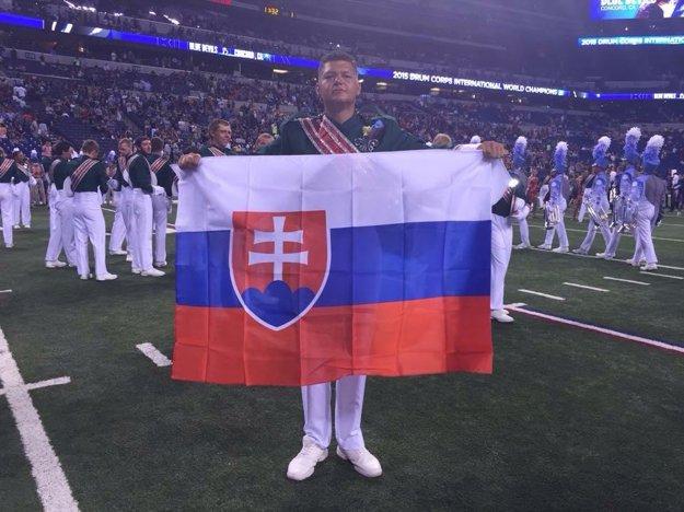 Talentovaný bubeník Samuel Kmotorka hrdo nesie zástavu Slovenskej republiky.