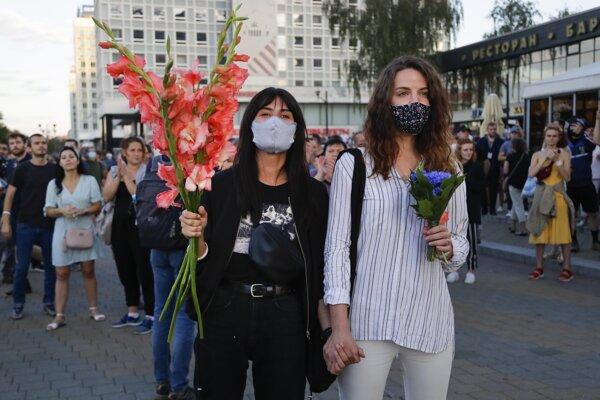 Ženy držia kvety a sledujú zásah polície počas protestov proti výsledkom prezidentských volieb v bieloruskej metropole Minsk v pondelok 10. augusta 2020.