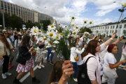 Ženy s bielymi kvetmi pochodujú za protestujúcich, ktorí boli zranení počas posledných protestných zhromaždení po nedeľných prezidentských voľbách 13. augusta 2020 v Minsku.