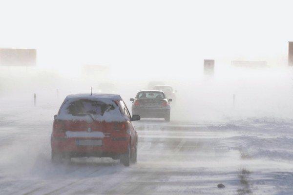 Autá prekonávajú snehové jazyky na ceste medzi Popradom a Starým Smokovcom v silnom vetre a hustom snežení.
