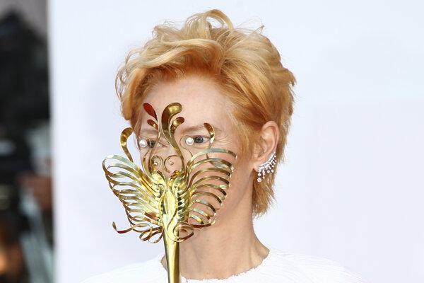 Herečka Tilda Swintonová drží karnevalovú masku počas príchodu na otvárací ceremoniál pri príležitosti otvorenia 77. ročníka medzinárodného filmového festivalu v Benátkach.