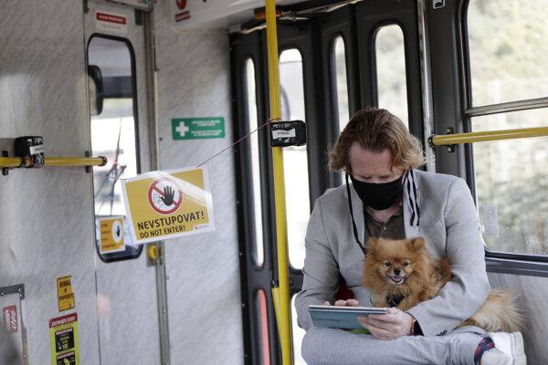 Cestujúci s ochranným rúškom sedí so psom na kolenách v električke pri kabínke vodiča, kde je nápis Nevstupovať v Prahe v stredu 23. septembra 2020.