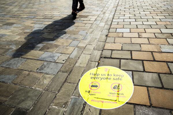 Výstražné upozornenie na dodržiavanie opatrení na chodníku v severoanglickom meste Leeds.