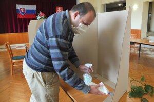 Dezinfekcia pier a stolov za plentami vo volebnej miestnosti v Bzenici.