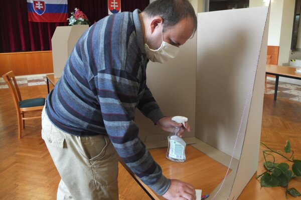 Člen volebnej komisie v Bzenici dezinfikuje miesto za plentou.