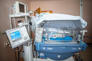 Inkubátor s dieťaťom, ktoré je pripojené na prístroje.