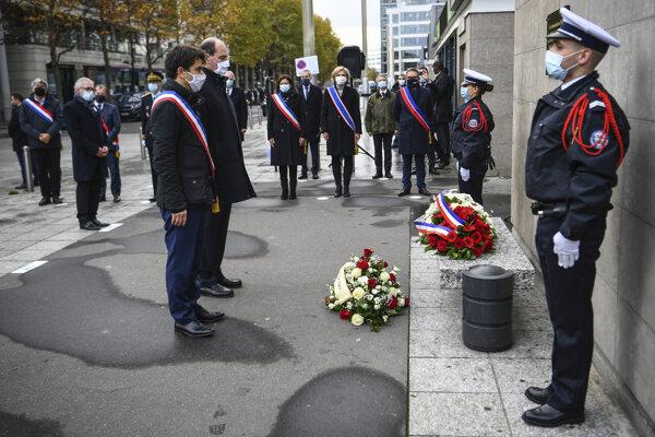 Starosta parížskej štvrti Saint-Denis Mathieu Hanotin (vľavo) a francúzsky premiér Jean Castex stoja pri pamätníku na pamiatku obetí parížskych útokov spred piatich rokov pred štadiónom v Saint Denis na predmestí Paríža.