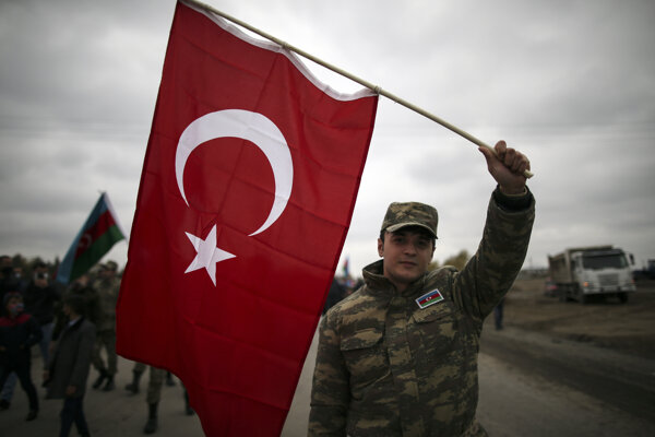 Azerbajdžanský vojak drží tureckú vlajku.